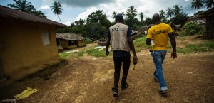 Elvis walks with Alex, a survivor of Ebola in Mawa Town