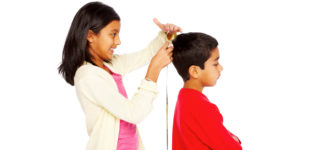 Cute little girl measuring height of her young brother on white background