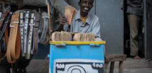 A money exchanger counts Somali shilling notes on the streets of the Somali capital Mogadishu. Millions of people in the Horn of Africa nation Somalia rely on money sent from their relatives and friends abroad in the form of remittances in order to survive, but it is feared that a decision by Barclays Bank to close the accounts of some of the biggest Somali money transfer firms – due to be announced this week - will have a devastating effect on the country and its people. According to the United Nations Development Programme (UNDP), an estimated $1.6 billion US dollars is sent back annually by Somalis living in Europe and North America. Some money transfer companies in Somalia have been accused of being used by pirates to launder money received form ransoms as well as used by Al Qaeda-affiliated extremist group al Shabaab group to fund their terrorist activities and operations in Somalia and the wider East African region. AU/UN IST PHOTO / STUART PRICE.